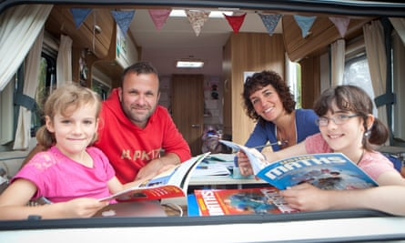 The Meek family pose for the camera in their caravan.
