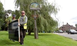 Workmen install solar panels at Balcombe Primary School, Sussex, UK