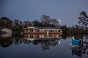 A home illuminated by moonlight sits still in the water of a flooded community at Rocky Point.