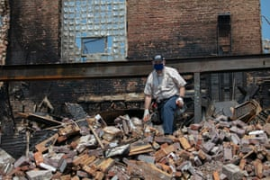 A man sifts through a destroyed building in the Uptown neighborhood of Kenosha.