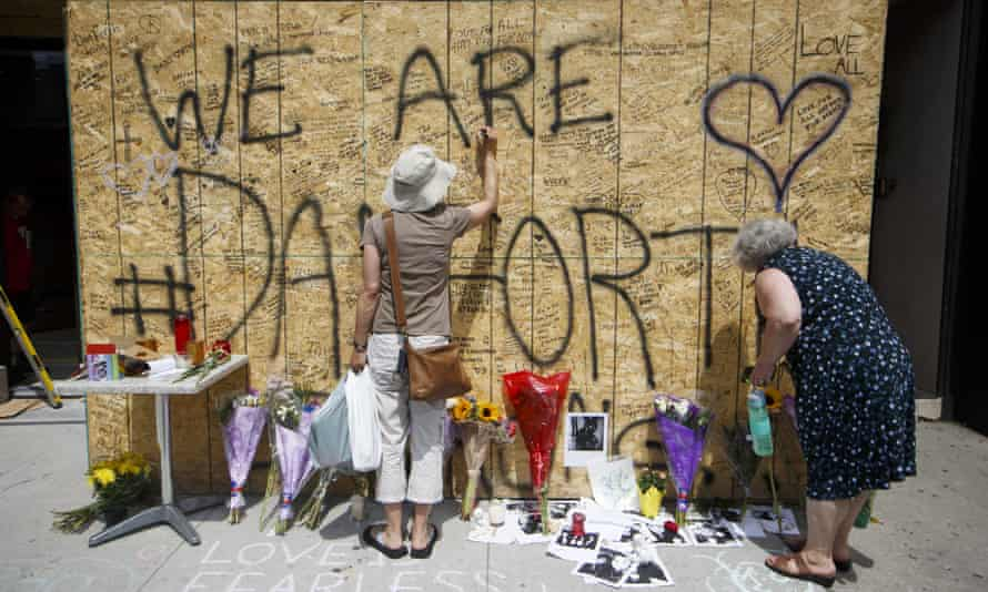 People sign a makeshift memorial on Danforth Avenue to honor and remember the victims of Sunday night's mass shooting on 24 July in Toronto, Canada.