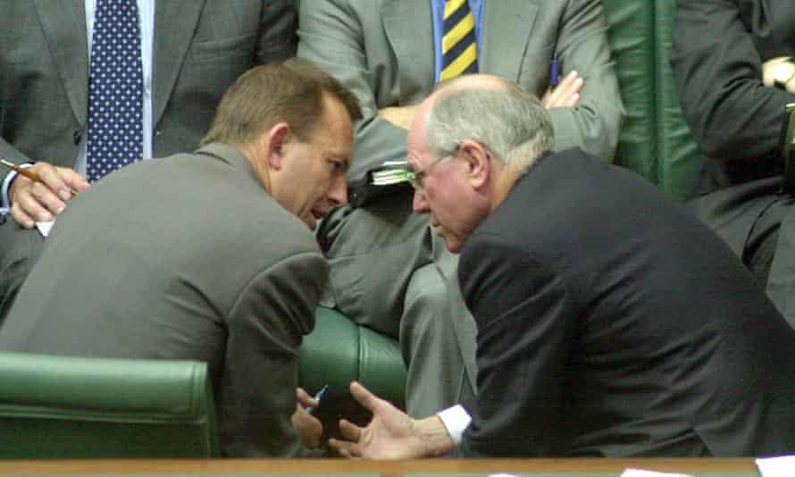 John Howard confers in parliament with his employment minister Tony Abbott, who went on to become prime minister.