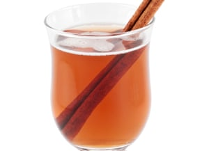 Glass mug of hot apple cider with a cinnamon stick, on white background
