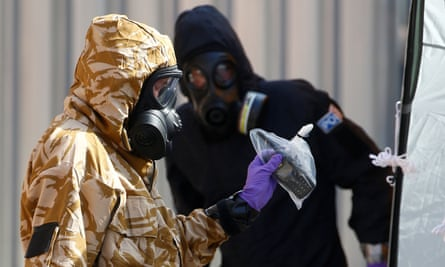 Forensic investigators in protective suits emerge from the rear of John Baker House in Amesbury, Wiltshire, one of the sites linked to recent novichok poisonings.