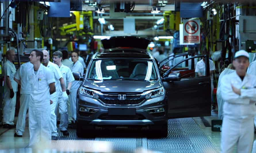 Workers surround a Honda car on the factory floor