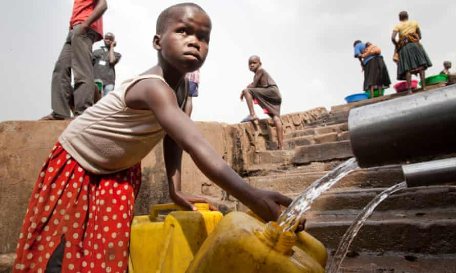 A child fills water cans in a slum in Kampala