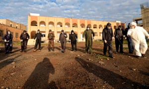 Security personnel disinfecting an area outside a security headquarters in Sanaa.