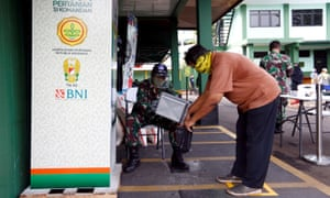A man wears protective face mask while receiving rice from an automated rice ATM distributor amid the spread of the coronavirus disease in Jakarta, Indonesia 4 May 2020.