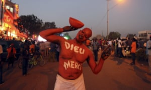 A supporter of Burkina Faso's president-elect Roch Marc Kabore wearing body paint that reads 'Thank God' in Ouagadougou in December.