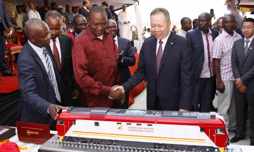 Kenyan President Uhuru Kenyatta, second left, and Chen Fenjian, president of CCC, shake hands at the opening of a Chinese-backed railway in Mombasa, Kenya, May 2017.