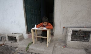 child writing at table in doorway