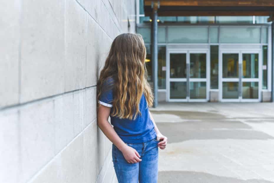 Teenage girl looking over her shoulder while leaning against a brick wall.