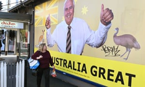 A woman walking past a billboard featuring United Australia party leader Clive Palmer. The workers of his company, Queensland Nickel, are still owed $7m.