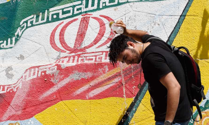 An Iranian cools off in front of a wall painting of Iran's national flag in Tehran.