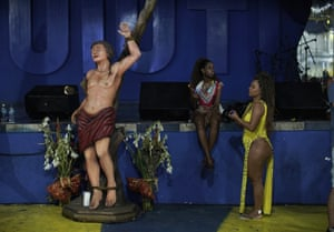 Performers wait next to a image of Saint Sebastian, the patron saint of the Rio de Janeiro