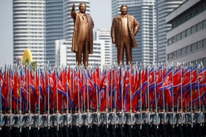 People carry flags in front of statues of North Korea founder Kim Il Sung and late leader Kim Jong Il