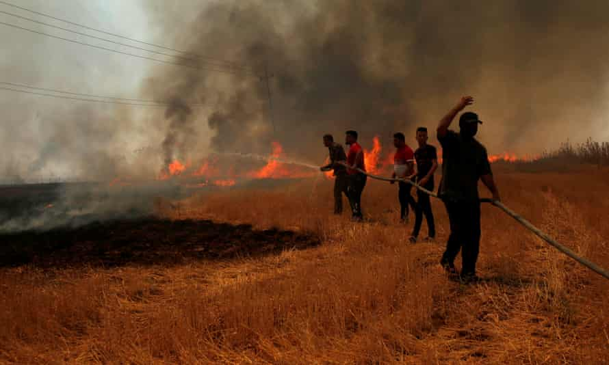 Iraqi farmers attempt to put out a fire that engulfed a wheat field in the northern town of Bashiqa, east of Mosul