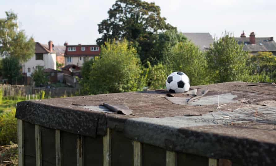 A lost football on top of a garage roof.