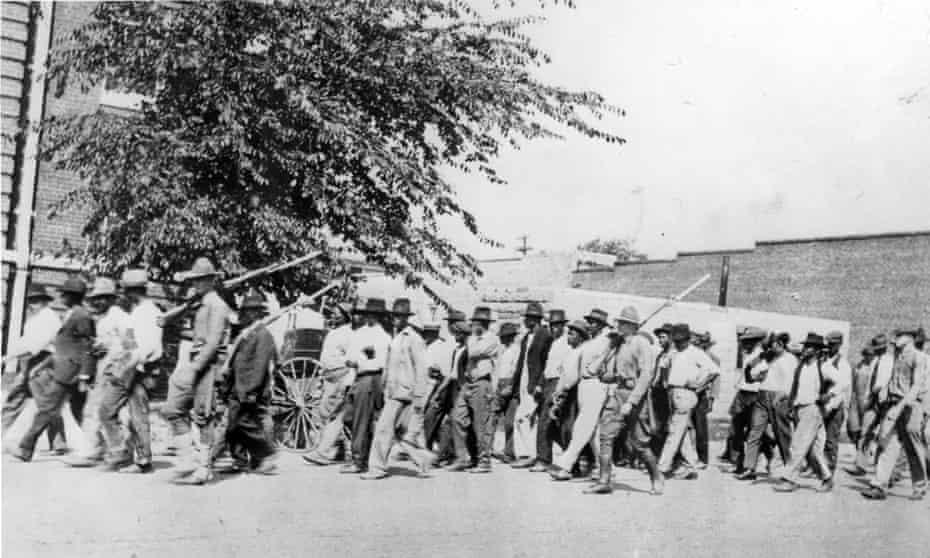 National guard troops escort unarmed African American men after the Tulsa Race Massacre in June 1921.
