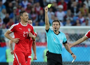Serbia's Nemanja Matic is shown a yellow card by referee Felix Brych.