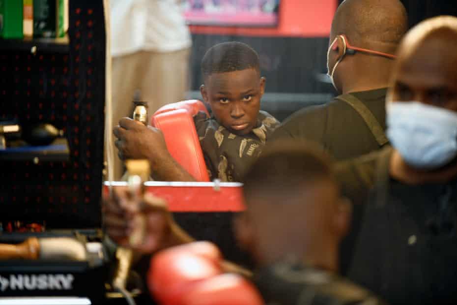 Camden Woods, 13, checks his haircut at Thomas's barber shop. Woods is vaccinated.