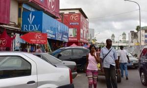 People walk through the Treichville market in Abidjan.