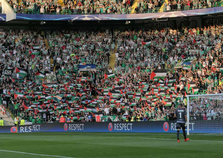 Celtic fans from the Green Brigade hold up large Palestinian flags during the Champions League qualifier between Celtic and Hapoel Beer Sheva.