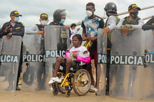 Friendship Bridge, Peru-Brazil border.  Police open the way to a woman in a wheelchair as a crowd of mixed-nationality migrants attempt to cross into Peru, 1,600km south-east of Lima