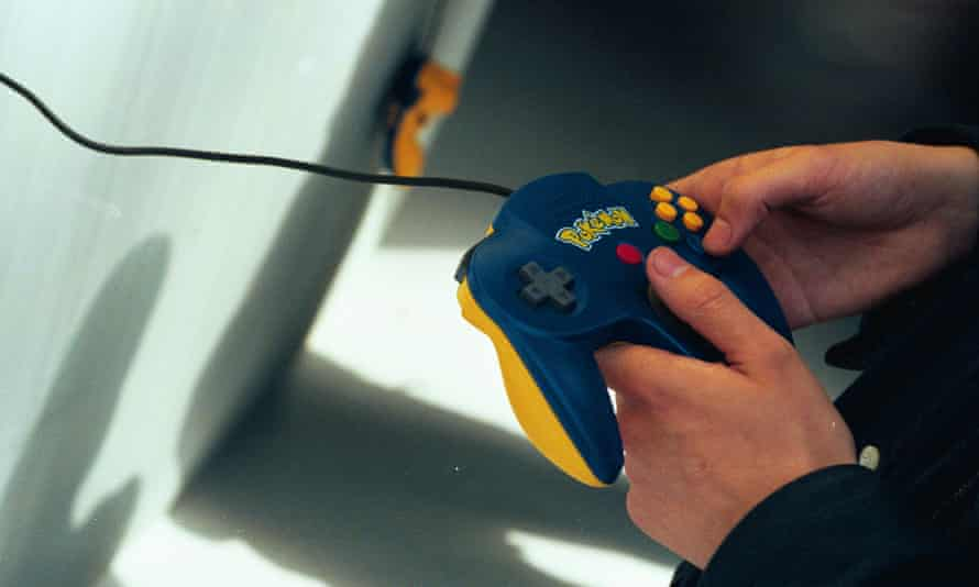 A person plays Pokémon Stadium using a special Pokemon controller on the N64.