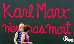 Women walk past a giant billboard that reads 'Karl Marx is not dead'