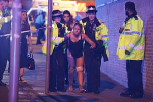 Police and other emergency services are seen helping a woman injured in the attack outside the Manchester Arena