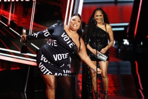 Lizzo accepts the Top Song Sales Artist award onstage in a Vote dress