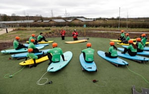 People on a surfing course listen to a briefing before their lesson at the The Wave, an artificial surfing lake in Bristol