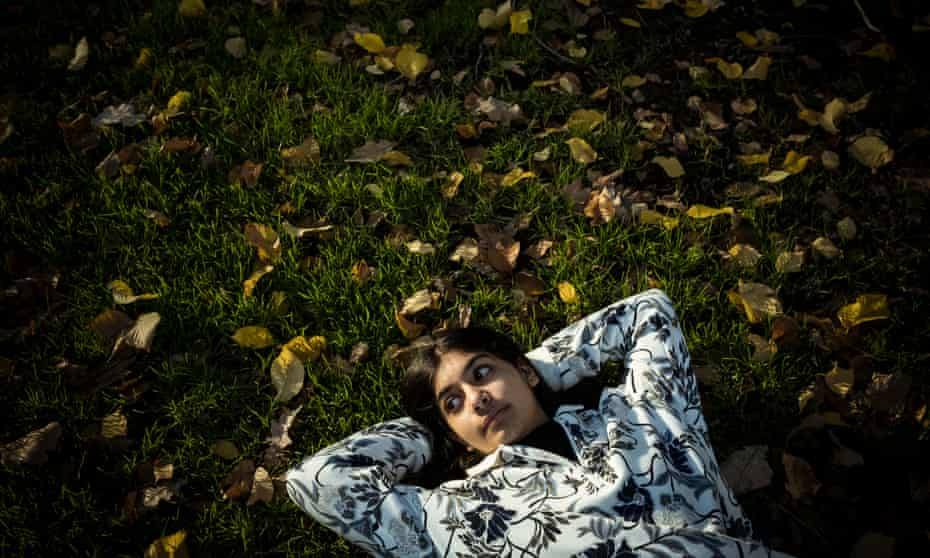a young girl lies on grass with fallen leaves with her hands behind her head