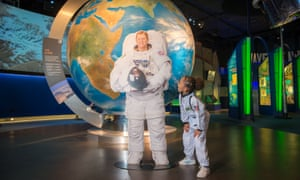 Cardboard cutout of astronaut Tim Peake in front of the National Space Centre's giant globe display. A child in space costume looks on.