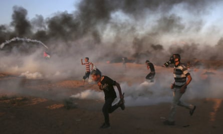Protesters run as teargas is fired by Israeli troops