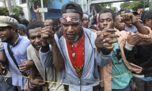 A Papuan activist bearing the banned separatist 'Morning Star' flag rallies with others in East Java on Saturday.
