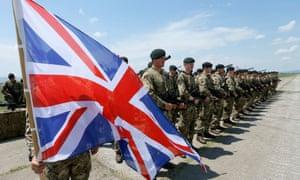 British servicemen line up next to a Union Jack