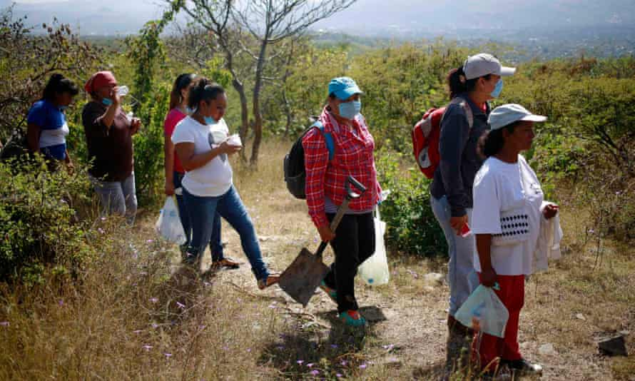 People with missing relatives walk to mass graves discovered in October, in La Joya on the outskirts of Iguala.