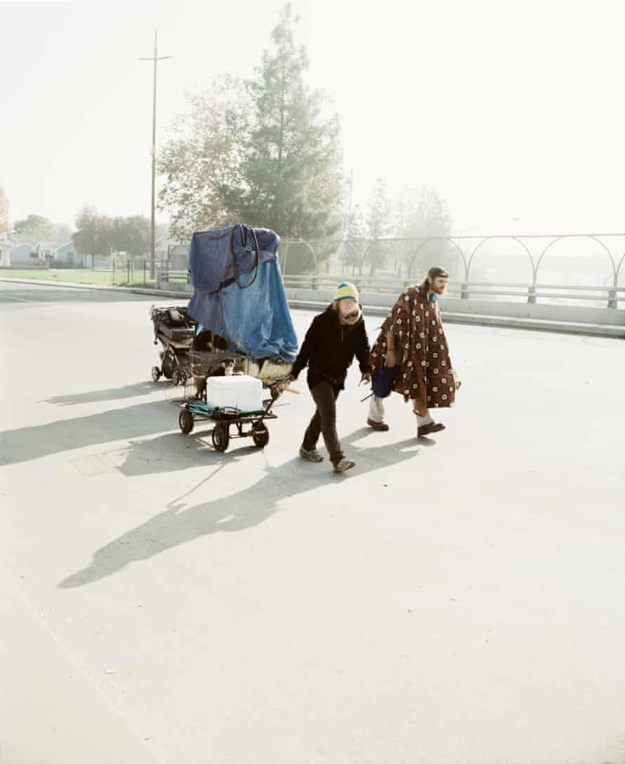 Couple pulling along possessions in carts and prams in Los Angeles