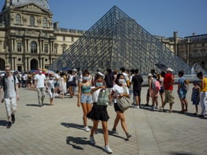 Visitors wearing protective face masks queue to enter the Louvre pyramid in Paris, France.