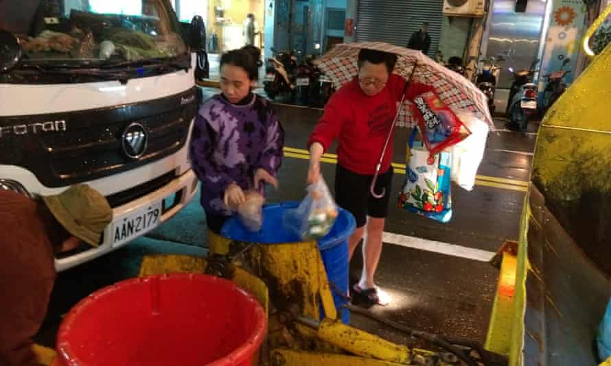 Taipei residents dump food scraps into waiting garbage trucks. Taiwan is one of a handful of countries that have institutionalized the practice of turning food waste into animal feed.