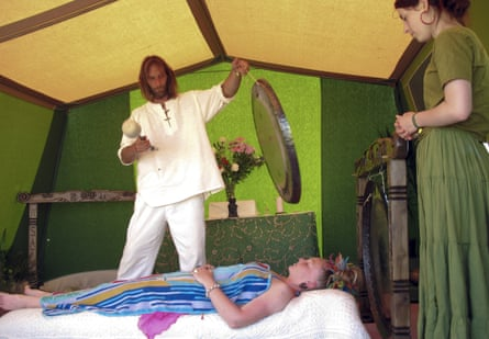 a client undergoes a gong bath cleansing ritual at a Festival in Somerset, Britain