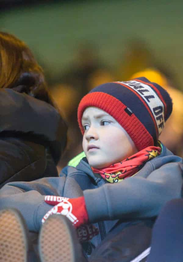 A young football fan watching the game