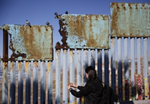 Tijuana, MexicoA woman takes pictures as birds sit along a rusted top section of the border wall near the beach.
