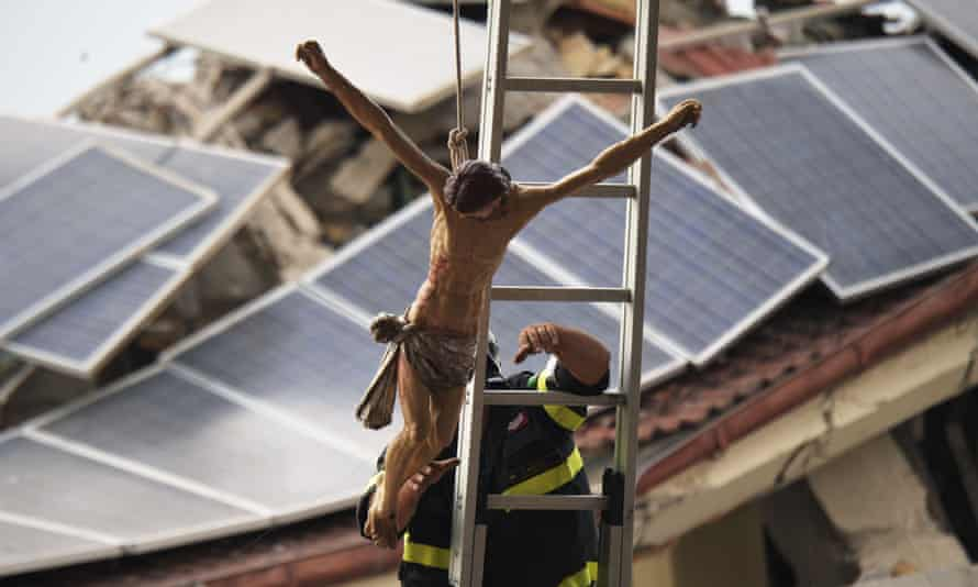 A firefighter hoists a crucifix into position before the state funeral.