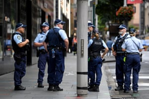 A group of police officers gather on a footpath in Sydney.
