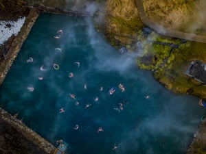 People swimming in a natural hot spring, the Secret Lagoon, Fludir, Iceland