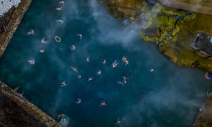 Aerial shot of people swimming in a natural hot spring: The Secret Lagoon, Fludir, Iceland