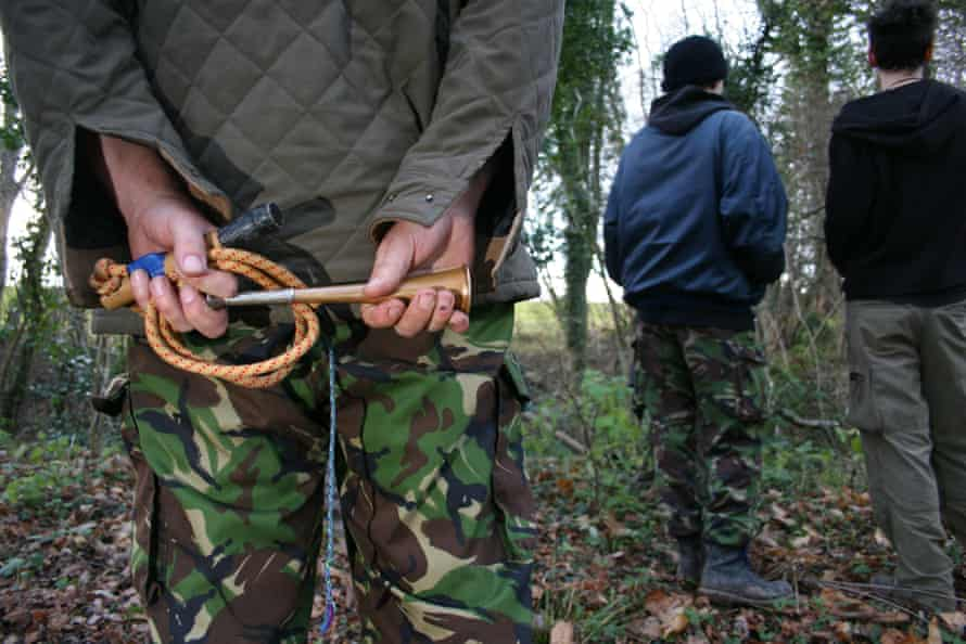 A hunt saboteur holding a hunting horn and home-made whip in Herefordshire.